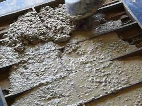 Фото: Закладка раствора в формы при изготовлении каменных плит