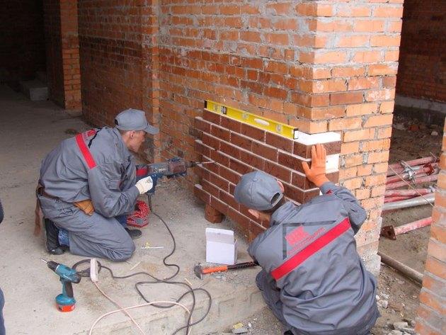 Фото: После выравнивания следует проделать отверстия в стене под крепеж