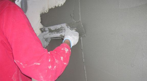 Фото: Нанесение фасадной шпатлевки на цементной основе