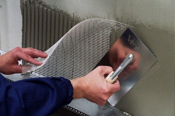 Фото: Наложение армирующей сетки выполняется широким шпателем